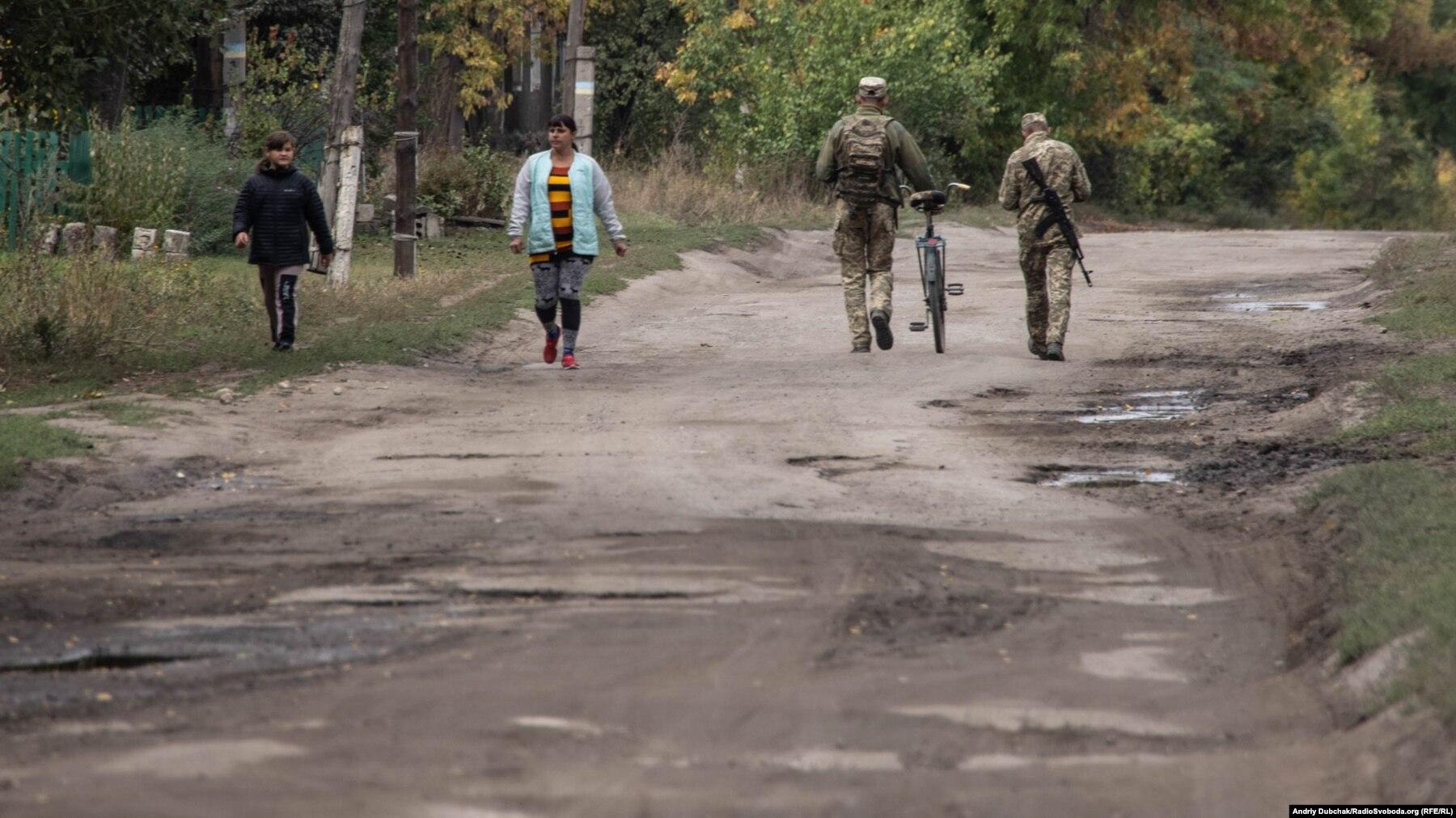 Донбас Фронтлайнер / Українські військові йдуть з позицій до магазину по вулиці Миру у фронтовому селищі Кримське, вересень 2021 року