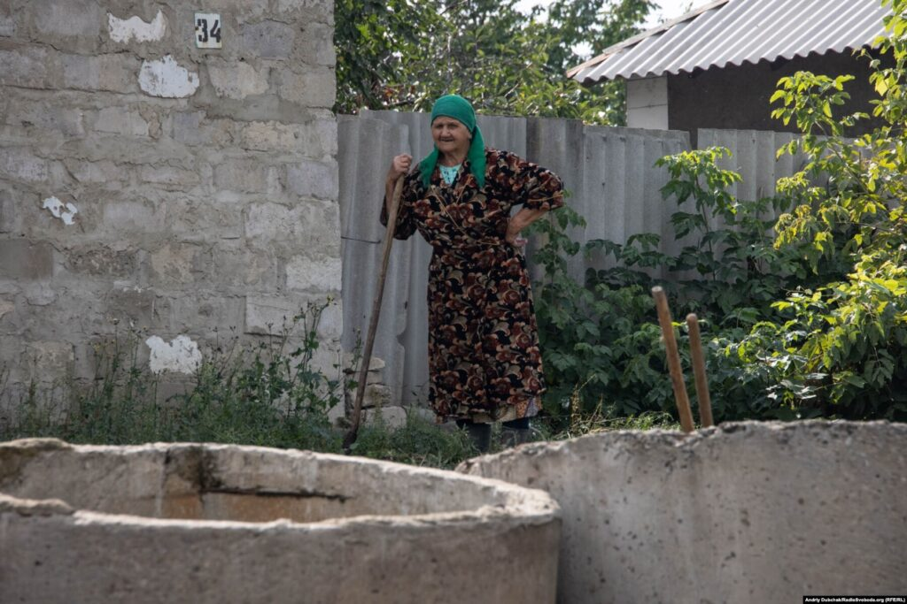 Донбас Фронтлайнер / Жінка біля бетонних кілець для криниці, Кримське, вересень 2021 року