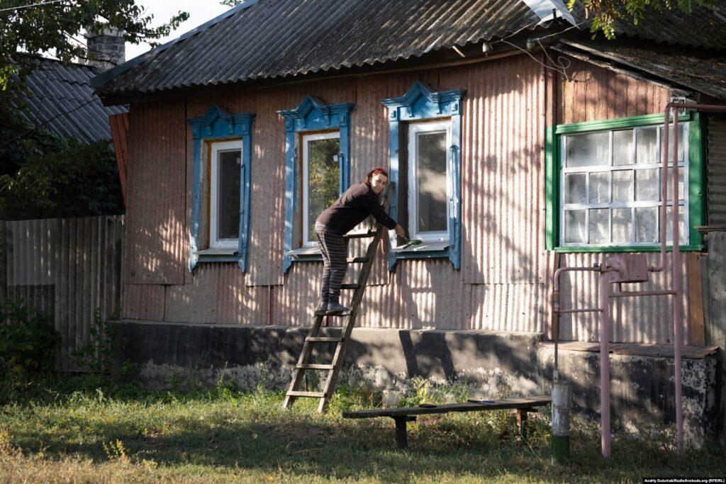 Мешканка Кримського ущільнює нові пластикові вікна перед сезоном холодів, вересень 2021 року